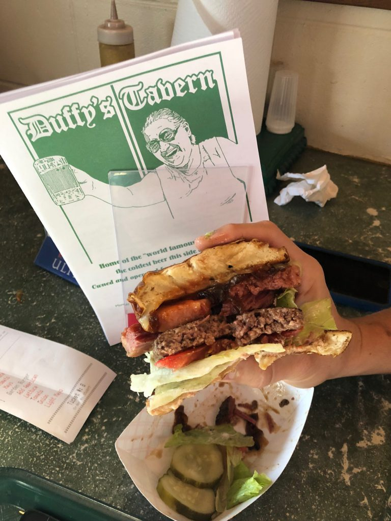 Person holding a burger at Duffy's