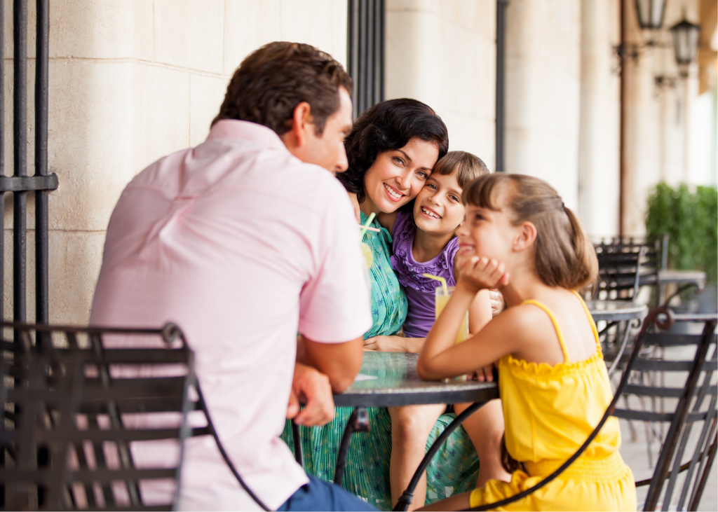 mom, dad, two daughters eating outside at a table