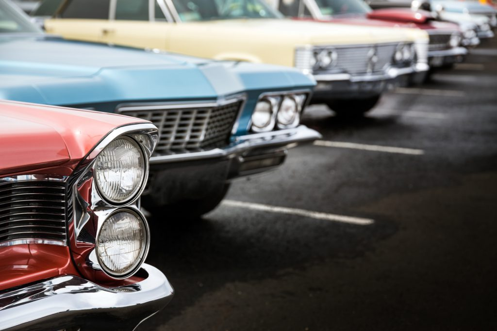 Classic cars in a row parked on asphalt parking lot